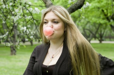 Playful blond girl blowing bubble with bubble gum