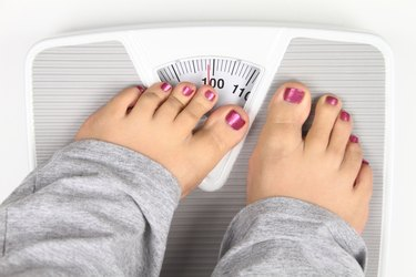Woman trying to hide what the scale is reading with toes