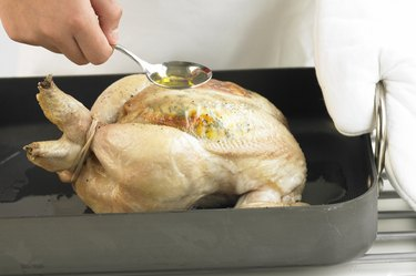 Seasoning a chicken in a roasting pan