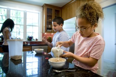 Kids eating cereal in kitchen