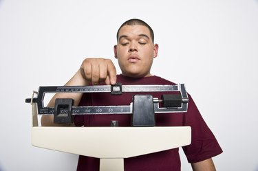 Teenage (16-17) boy using weight scales