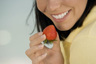 Close-up of a young woman holding a strawberry on the beach