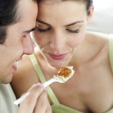 close-up of a young man feeding a young woman with a plastic fork