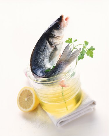 Raw fish, cooking oil, chervil, lemon and napkin on white background, close-up