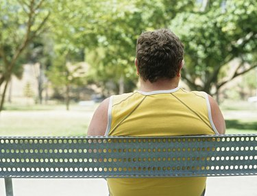 Overweight man sitting on bench in park,rear view