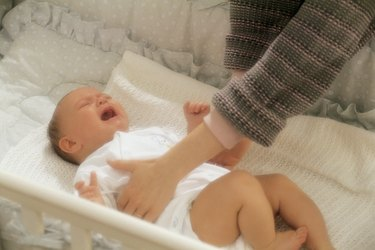 Mother reaching for crying baby in crib