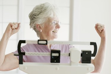 Senior woman weighing self on scale and cheering
