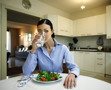 Woman with salad drinking water