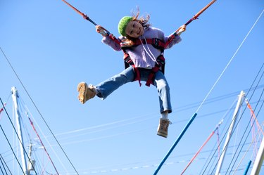 Girl jumping on trampoline with bungee cords