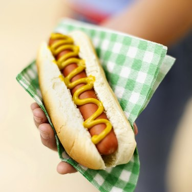 close-up of hand holding hot dog in napkin