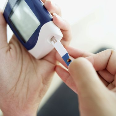 close up of a woman using a glucometer