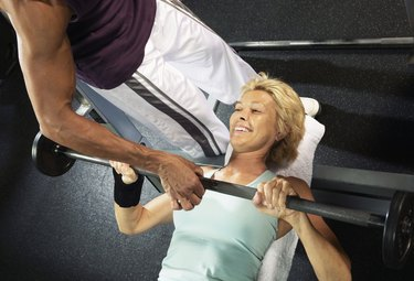 Mature woman lifting weight guided by male instructor, smiling