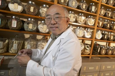 Senior Chinese-herbalist in store, holding plastic glove, smiling, portrait