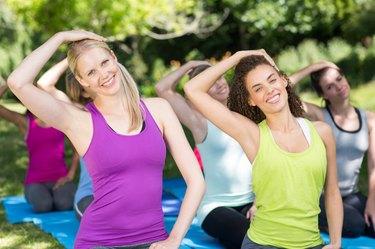 Fitness group doing yoga in park