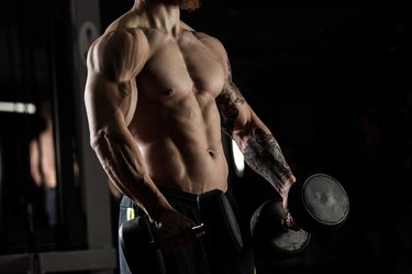 bodybuilder with dumbbells in a gym, exercising with a barbell