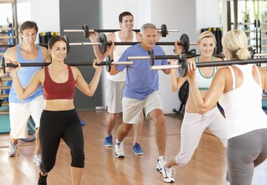 Group Of People Lifting Weights In Gym