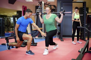 Individual training. Plus sized woman working out with personal trainer