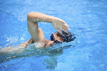 Young man swimming a fast freestyle stroke in a pool