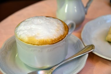 Delicious cappuccino on a white cup on a table