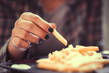 woman hand with green nails toasting french fries in restaurant