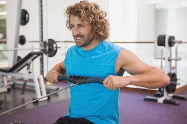 Handsome man using resistance band in gym