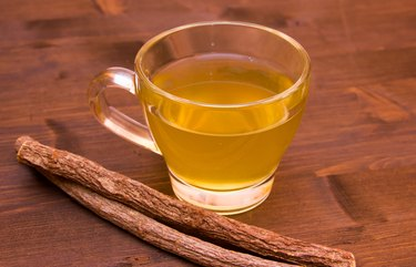 Herbal tea licorice inside cup on wood