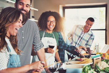 Group of diverse friends drinking and cooking