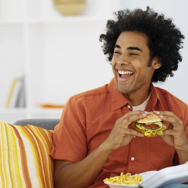 Close-up of mid adult man eating burger and French fries