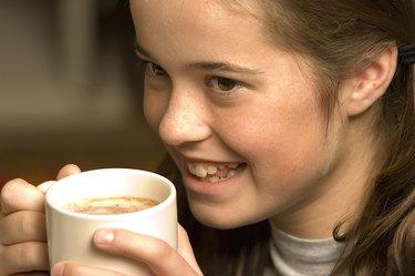 Teenage girl with hot beverage