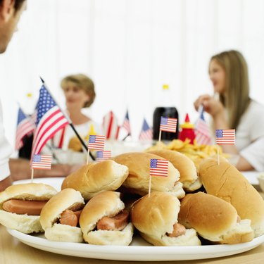 Close-up of a platter of hotdogs dotted with miniature American flags