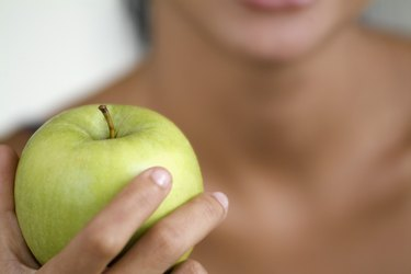 A person holding an apple