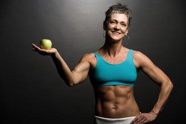 Body builder holding an apple
