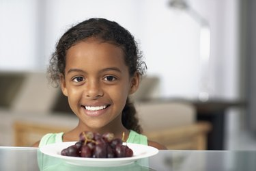 Mixed Race girl with plate of grapes