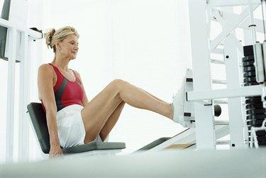 Senior woman using leg press machine in a gym