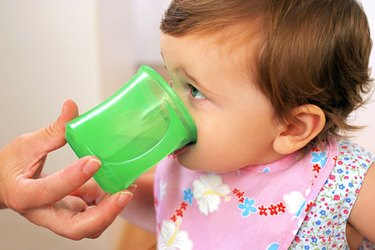 A baby girl drinks from a green cup with help from her mother.