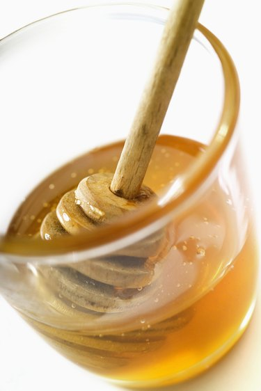 Honey dipper in jar of honey, close-up, tilt