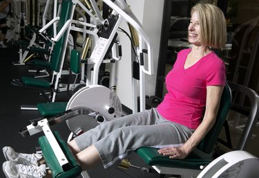 Senior woman lift leg weights in gym, smiling
