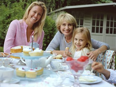 Three generation family of females at garden table, smiling