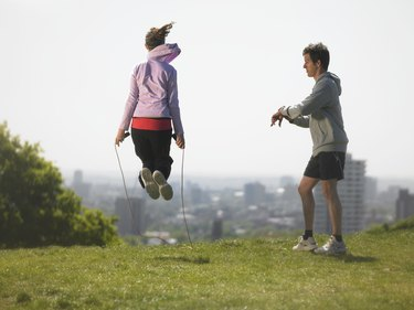 Man timing woman skipping, city in background