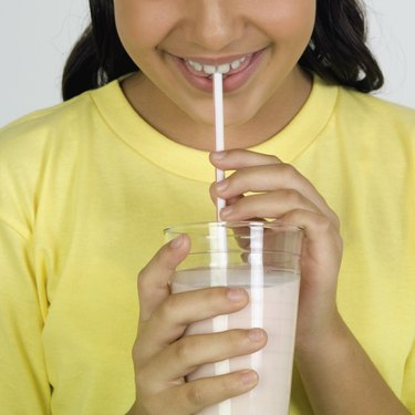 Girl drinking milk, close-up, part of