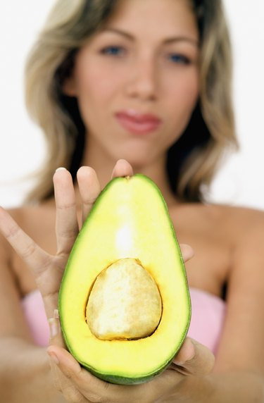 Young woman holding out half of an avocado, close-up, selective focus, focus on hand and avocado