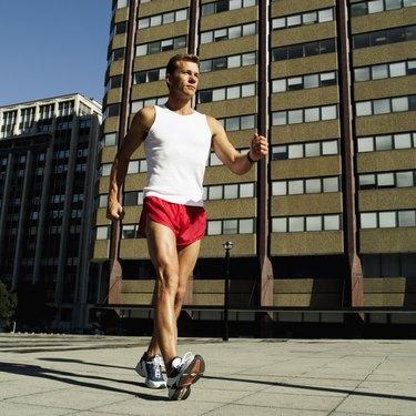 Side profile of a man wearing shorts power walking outdoors