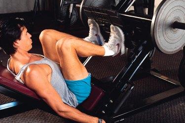 Man doing leg lifts at gym