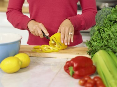 mid section view of a woman cutting a yellow bell pepper