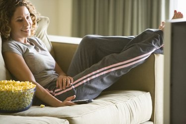 Mid adult woman on sofa watching tv