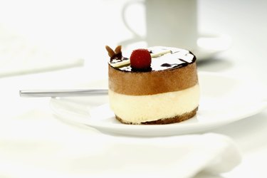 Ornate cheesecake on plate with coffee cup in background, close-up, selective focus