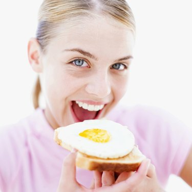 Close-up of a teenage girl (16-18) eating a fried egg on toast