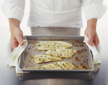 Four pieces of baked plaice fillets on a baking tray