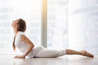 Young attractive happy woman practicing yoga, doing Cobra exercise, Bhujangasana pose, working out, wearing sportswear, white t-shirt, pants, indoor full length, near floor window with city view