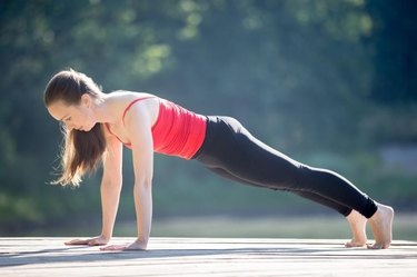 Beautiful sporty fit young woman in sportswear working out outdoors on summer day, doing plank posture, exercises for abs muscles, full length